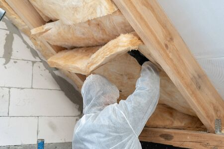 Back view of unrecognizable professional worker man in protective uniform installing thermal insulation layer under the roof. Man holding and fixed material on mansard wall