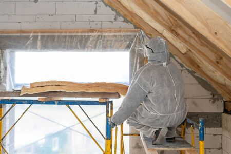 Back view of professional roofer man in protective overall installing thermal insulation layer with fiberglass wool under the roof. Man sitting near scaffolding against brick wall with window