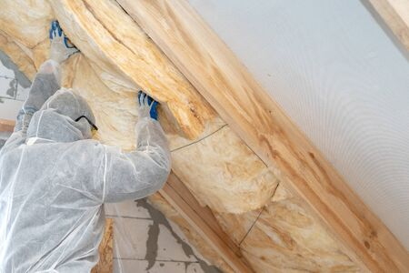 Professional workman in protective uniform installing thermal insulation layer under the roof. Man holding material and fixed it on wall with copy space