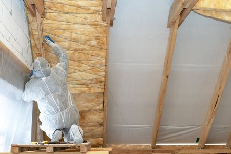 Back view of professional foreman in protective uniform installing thermal insulation rock wool under the roof, fixed material on wall