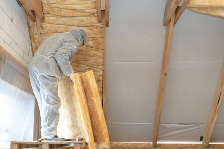 Back view of professional workman installing thermal insulation layer with mineral rock wool under the roof. Man in protective overall holding material in hands, standing near wall