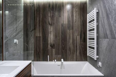 Weißes und modernes Bad im neuen zeitgenössischen Badezimmer mit modernem und elektrisch beheiztem Handtuchhalter an der Wand in der neuen Wohnung Standard-Bild