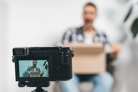 Selective focus on camera with excited young adult successful blogger using broadcast equipment, creative online video content for social media, sitting in studio, holding carton box in hands