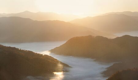 Sunrise in peaceful and scenic valley with beautiful nature landscape at autumn mountain with misty fog