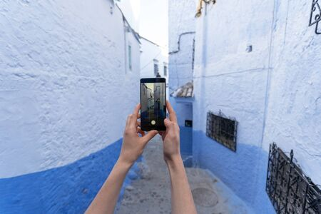Cropped view of woman holding modern smartphone in hand, making street photo with blue walls on city buildings and copy space 写真素材 - 136809442