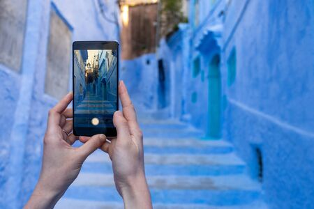 Cropped view of woman holding modern smartphone in hands, making photo with blue wall background and copy space 写真素材
