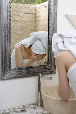 Back view of young adult woman washing face with splashing water above bathroom sink, standing near mirror in washroom 写真素材 - 136809613