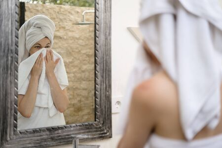Back view of young adult woman standing in bathroom, looking at mirror reflection, wiping face with white towel