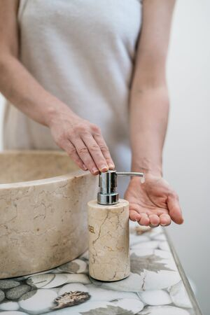 Cropped view of young adult woman standing in bathroom, washing hands, pump soap from bottle and making morning routine procedure 写真素材 - 136809640