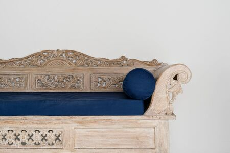 Wooden and carved couch with blue cushion near white wall in house with stylish traditional interior room and copy space  on background 写真素材 - 136809645