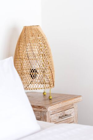 Cozy bedroom, white linen and wicker night lamp on bedside table at modern house interior with copy space on wall