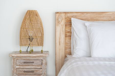 Element on modern interior, cozy bed in comfort bedroom, white linen, pillows and wicker night lamp on bedside table in house 写真素材
