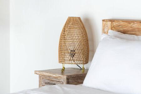 Comfort bed in cozy bedroom with wicker night lamp on bedside table at modern house interior standing near copy space on wall