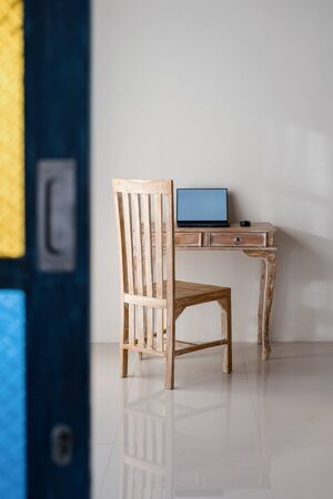 Modern laptop computer with copy space on display on wooden table in house with white walls 写真素材 - 136809702