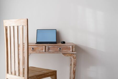 Laptop computer with copy space on display monitor on wooden table in house with chair and white wall in room 写真素材 - 136809703