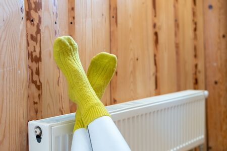 Heating system concept. Selective focus on cropped woman legs in yellow socks over modern radiator at wooden wall with copy space in house with cozy interior 写真素材 - 136735940