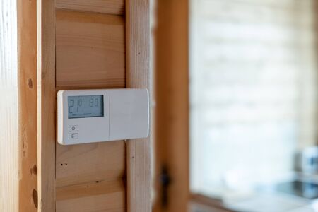 Smart home system on wooden wall in modern house with cozy living room interior against blurred background and copy space 写真素材
