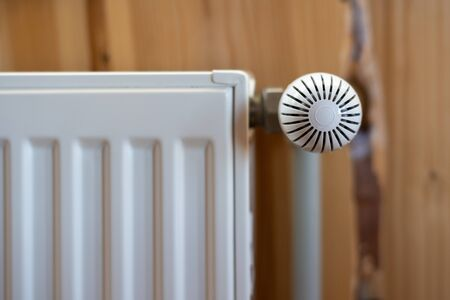 Heating system concept. Close up of modern radiator with heat controller in room at copy space on wooden wall and cozy interior