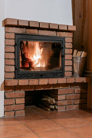Fireplace with flame and glass door in comfort house. Metal basket with firewood near fire chimney at cozy interior in living room 写真素材 - 136735011