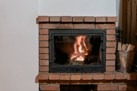 Fireplace with fire and glass door in comfort house, white copy space on background wall. Metal basket with firewood near fire chimney at cozy interior in lounge room 写真素材 - 136736043