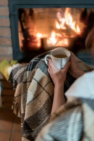 Cropped view of young adult woman sitting with cup of beverage near fireplace in comfort house. Girl spending weekend day at home 写真素材 - 136809714