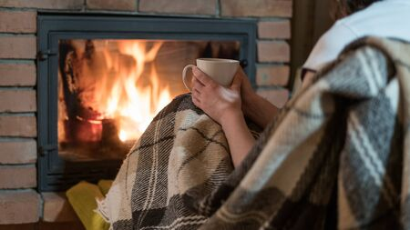 Cropped view of young adult woman covered in plaid, sitting near fireplace with fire and glass door in comfort house. Girl sitting at home with cup of beverage 写真素材 - 136734982