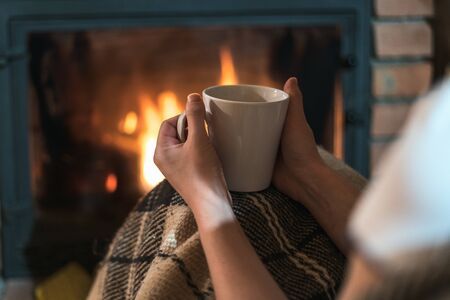 Cropped view of young adult girl with cup of tea or coffee sitting near fireplace in comfort house. Woman enjoying beverage at home 写真素材 - 136809715