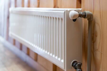 Heating season concept. Selective focus of white modern radiator with heat controller on wooden wall in house with cozy interior