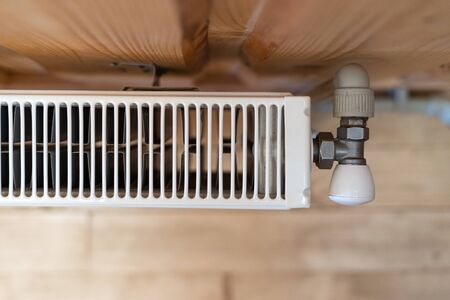 Heating system concept. High angle and top view of modern radiator in room with copy space on wooden wall and cozy interior 写真素材 - 136809716