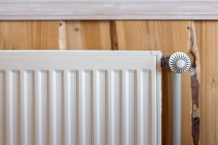 Heating system concept. White modern radiator with temperature controller in living room with wooden wall and cozy interior 写真素材 - 136736159