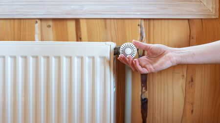 Heating season concept. Panoramic view of woman hand adjusting temperature on modern radiator at wooden wall in house with cozy interior 写真素材 - 136734981