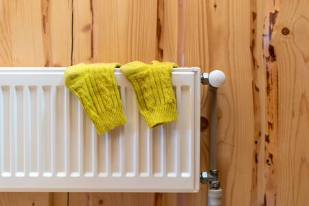 Heating system concept. Close up yellow socks at white modern radiator on wooden wall in house with cozy interior 写真素材 - 136735823