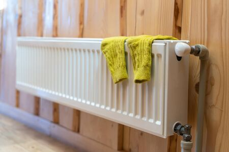 Heating season concept. Selective focus of yellow socks on modern radiator in room with wooden wall and cozy interior 写真素材 - 136734997