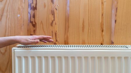 Heating system concept. Cropped view of woman holding hand over modern individual radiator, checking warmth. Battery on wooden wall in house with cozy interior