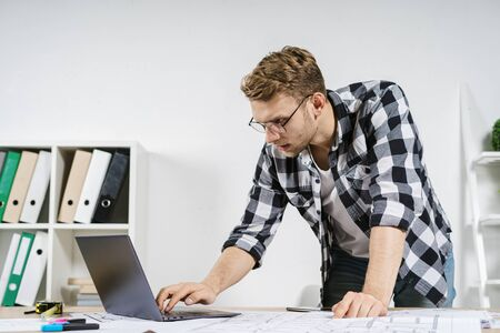Focused and concentrated young adult architect working with blueprints in workspace office, using laptop computer, searching information online