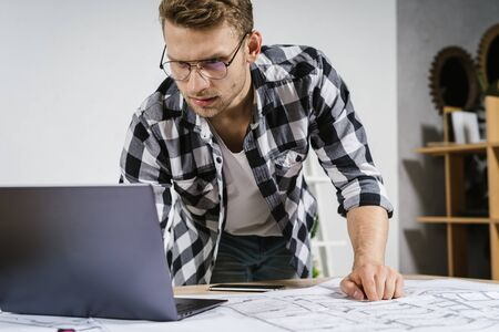 Educated and young adult architect businessman working in modern studio with blueprints, using laptop computer, looking at display and standing behind table
