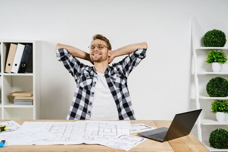 Dreamy and happy young adult architect freelancer working with blueprints in workspace office, holding hands behind head, smiling wide and resting after finish project 写真素材