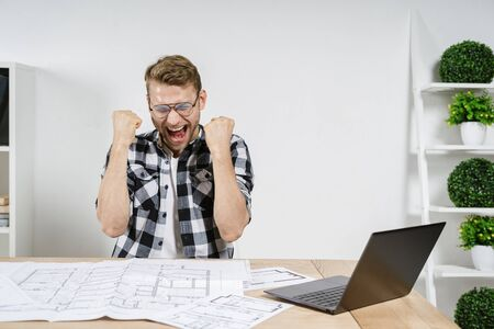 Rejoiced and happy young adult architect celebrated success, screaming, raised fists up, sitting against wall with copy space, working with blueprints in workplace studio 写真素材
