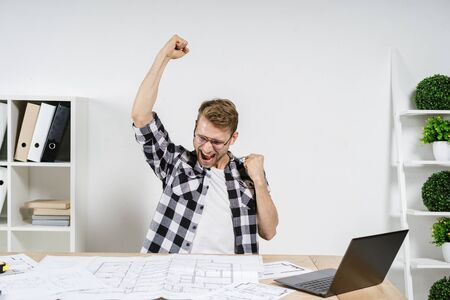 Successful and excited young adult architect freelancer celebrating triumph after working in professional bureau with blueprints, looking at laptop computer, raised fists up