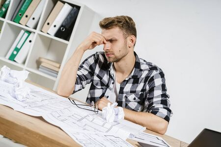Tired young adult architect businessman working in modern studio with blueprints, feeling headache, making upset, exhausted face sitting behind table against background with copy space