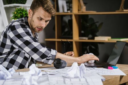 Worried young adult architect businessman spilling coffee on documents, working in modern studio with blueprints, sitting behind table with shocked face