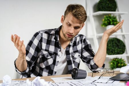Exhausted and unhappy young adult architect freelancer working with blueprints in workspace office, spilling coffee on documents, sitting behind table, making tired frustrated face