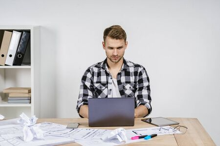 Confident and successful young adult architect designer using laptop computer, working with blueprints in workspace office, making calm face, sitting behind wall with copy space