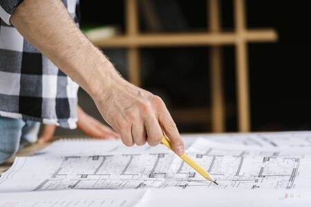 Cropped view of young adult architect working with blueprints in workplace studio, pointing at documents with pencil, choosing solutions for reconstruction house 写真素材