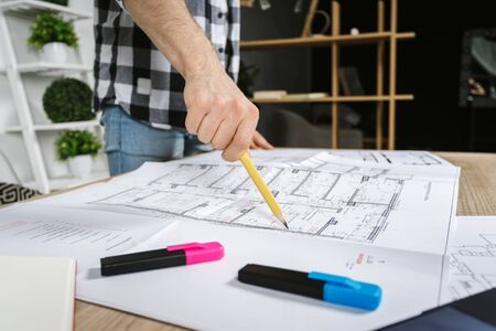 Cropped view and selective focus of young adult architect freelancer pointing at documents with pencil, working in professional bureau with blueprints