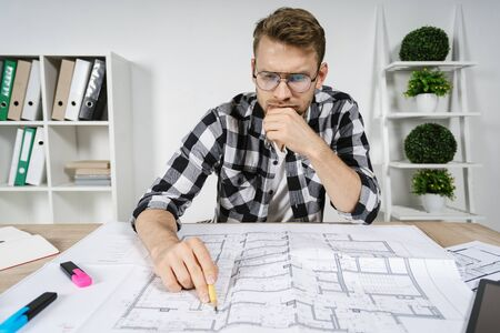 Minder and smart young adult architect working with blueprints in workspace office, checking solution for interior design in new house, making thoughtful face 写真素材