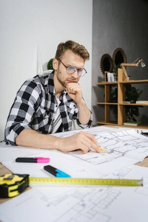 Thoughtful young adult architect businessman working in modern studio with blueprints, looking at housing project and thinking about renovation solution 写真素材
