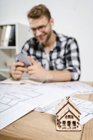 Selective focus on new house symbol against blurred background with young adult project manager and architect working with blueprints in workplace studio, smiling, using smartphone app