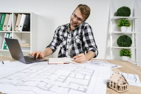 Happy and busy young adult architect working in professional bureau with blueprints, making interior design for house, using laptop computer, talking on smartphone with client 写真素材