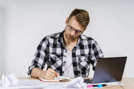 Young adult architect businessman working in modern studio with blueprints, using laptop computer, writing notes about new construction project in organizer, sitting against wall with copy space 写真素材